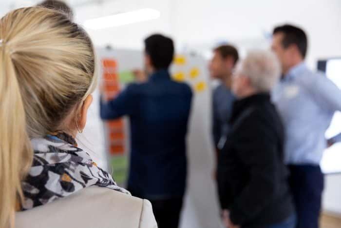 Kunden von Me & Company arbeiten im Hintergrund am Whiteboard im Rahmen des Zukunftsträger Programms