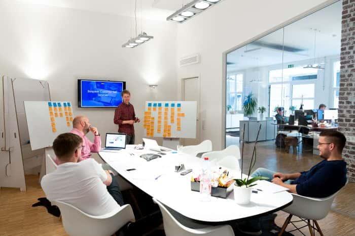 Mitarbeiter von Me & Company sitzen zusammen mit Bewerber im Konferenzraum