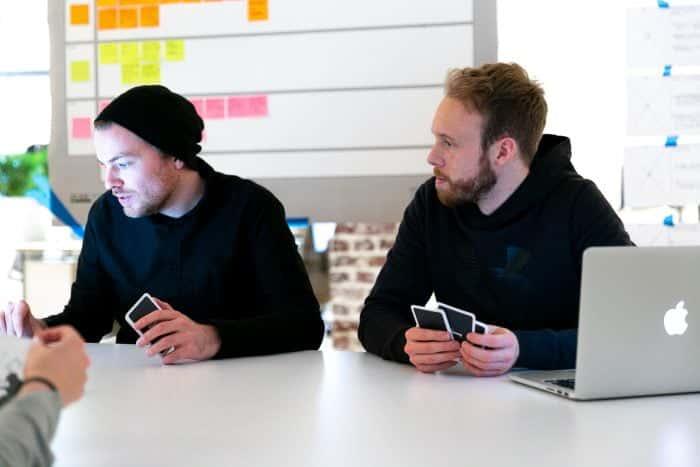 Zwei Mitarbeiter von Me & Company mit Planning Poker Karten vor Laptops