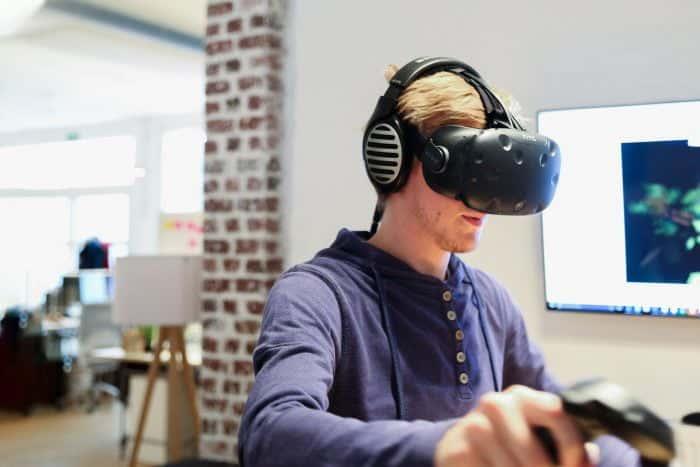 Mitarbeiter von Me & Company spielt ein VR-Spielt und trägt die HTC Vive