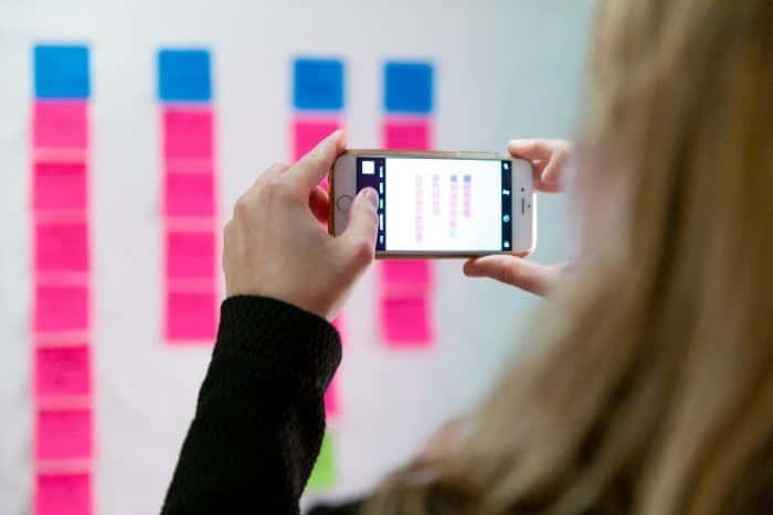 MItarbeiterin von Me & Company schießt mit ihrem Smartphone ein Bild von Post-its