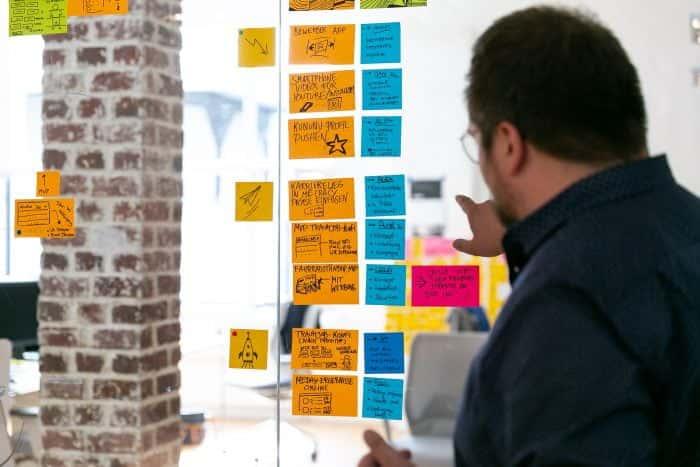 Mitarbeiter von Me & Company bespricht das Systemwechsel Programm anhand von Post-its