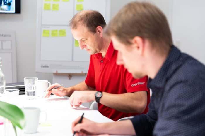 Mitarbeiter von Me & Company arbeitet gemeinsam mit einem Kunden einen Entwurf im Rahmen des Digitalwerk Programm aus