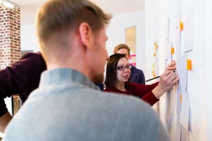 Mitarbeiter von Me & Company führen Bewerber am Whiteboard durch Probearbeitstag