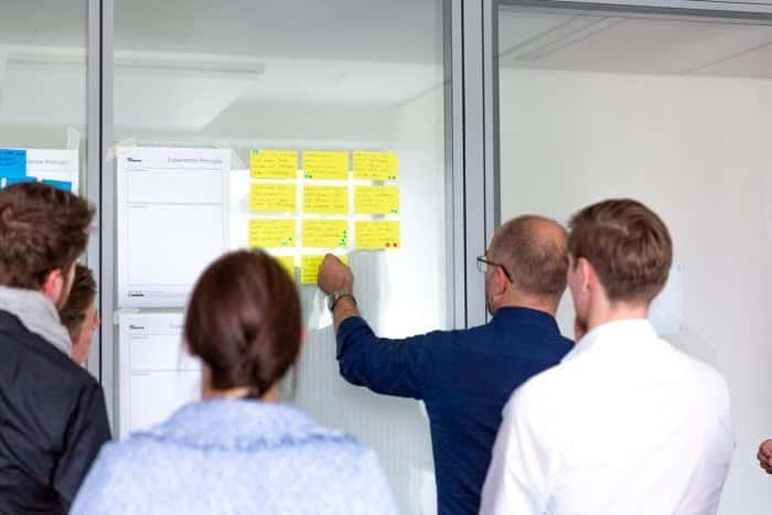 Kunden von Me & Company arbeiten mit Post-its an New Work Themen