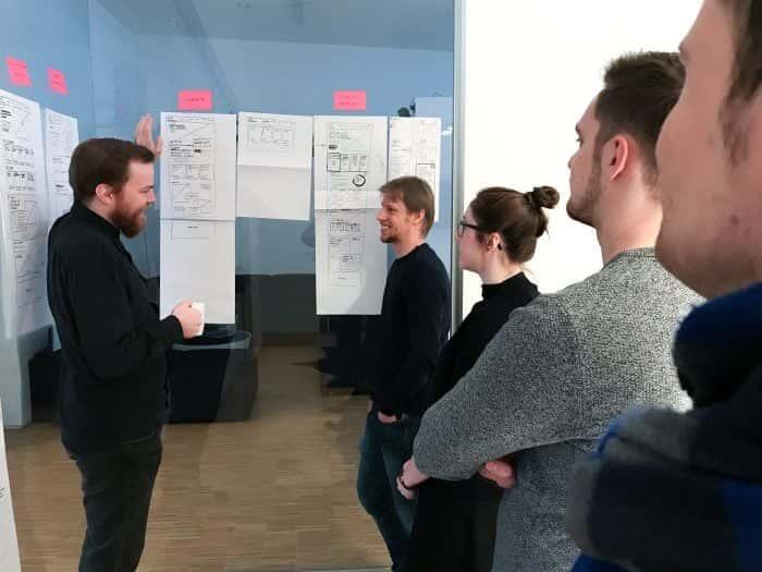 Mitarbeiter von Me & Company diskutieren Papier Prototypen von Webseite