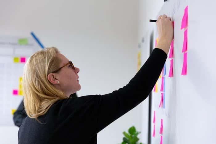 Mitarbeiterin von Me & Company schreibt im Rahmen der Design Thinking Masterclass aus Post-it