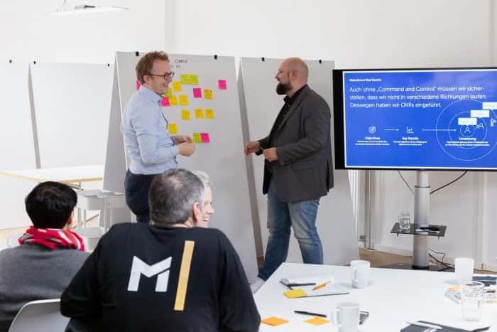 Mitarbeiter von Me & Company steht zusammen mit Kunden der Metro AG vor Whiteboard