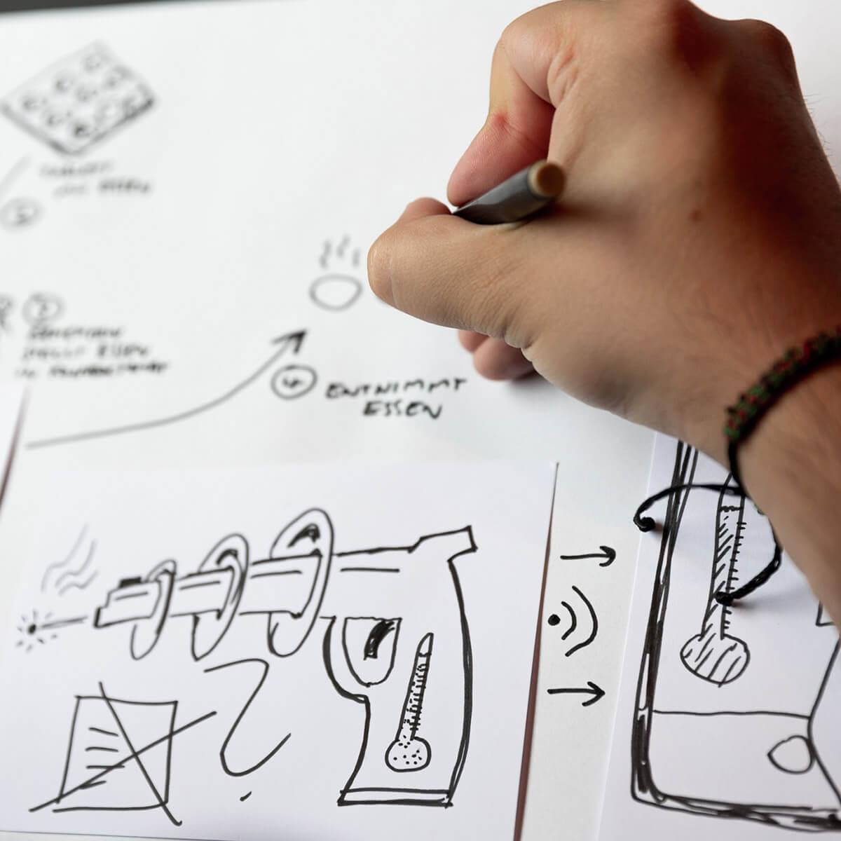 Mitarbeiter von Me & Company zeichnet auf Papier in der Rolle als Brand Designer