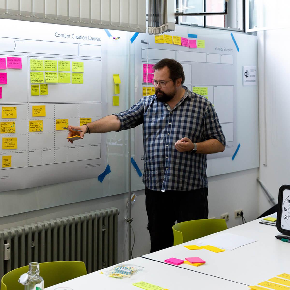 Mitarbeiter von Me & Company steht vor Canvas in seiner Rolle als Business Strategist