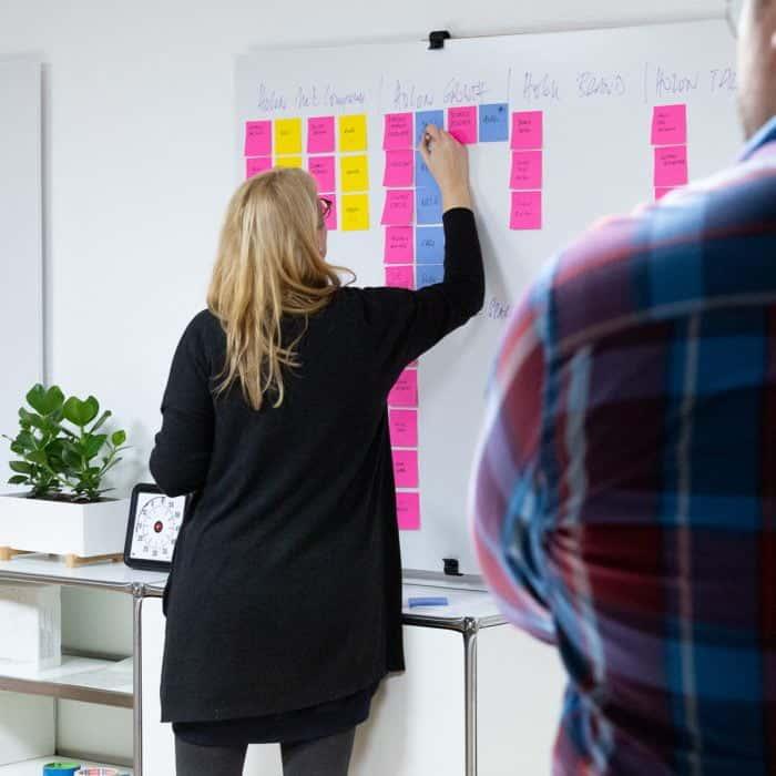 Mitarbeiterin von Me & Company arbeitet mit Post-its am Whiteboard im Rahmen ihrer Rolle als Growth Hacker