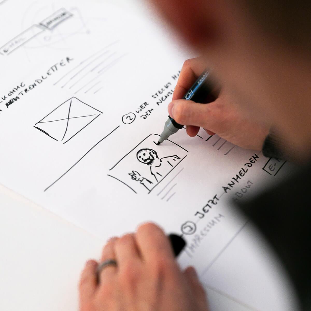 Mitarbeiter von Me & Company zeichnet Prototypen von Webseite im Rahmen seiner Rolle als Interface Designer