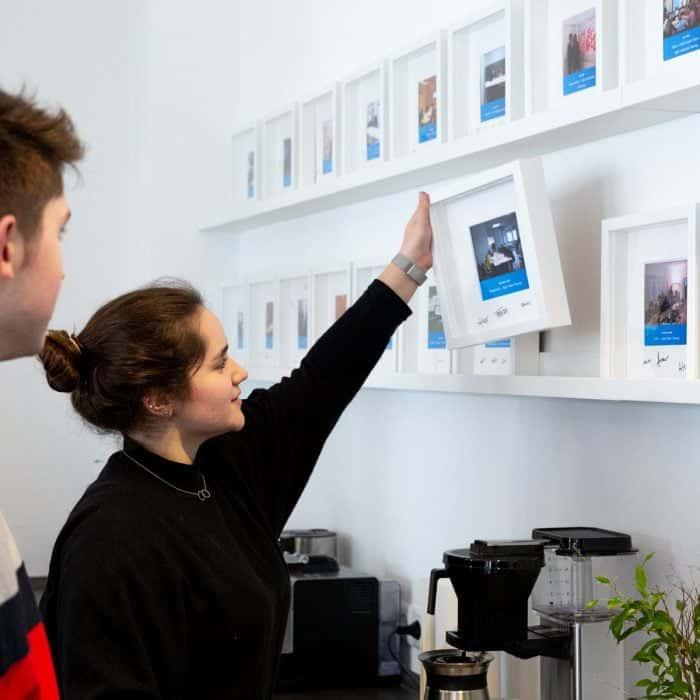 Mitarbeiterin von Me & Company hält in ihrer Rolle als Team Support Bilderrahmen in der Hand